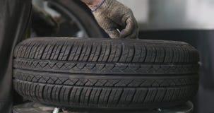 Il meccanico di automobile professionista sostituisce la gomma sopra spinge dentro il timelapse di servizio di riparazione automa video d archivio