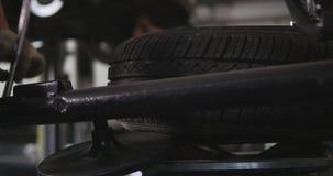 Il meccanico di automobile professionista sostituisce la gomma sopra spinge dentro il timelapse di servizio di riparazione automa archivi video
