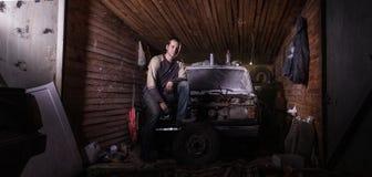Il meccanico di automobile russo in un garage ripara l'automobile Fotografia Stock Libera da Diritti