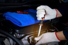 Il meccanico di automobile sta utilizzando una chiave fotografia stock