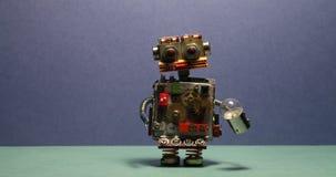 Il meccanico divertente del robot cammina ed ondeggiando le sue armi Cyborg del giocattolo con la lampadina Fondo blu del pavimen video d archivio