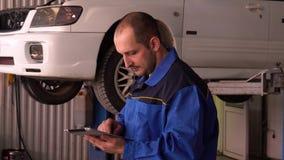 Il meccanico esamina le letture dei sistemi diagnostici elettronici di un'automobile facendo uso di una compressa digitale video d archivio