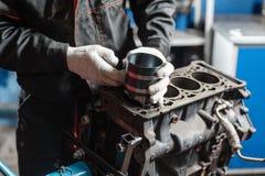 Il meccanico installa un nuovo pistone Smonti il veicolo del blocco motore Riparazione del capitale del motore Sedici valvole e q immagini stock