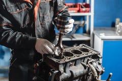 Il meccanico installa un nuovo pistone Smonti il veicolo del blocco motore Riparazione del capitale del motore Sedici valvole e q fotografia stock libera da diritti