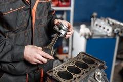 Il meccanico installa un nuovo pistone Smonti il veicolo del blocco motore Riparazione del capitale del motore Sedici valvole e q fotografia stock