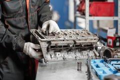 Il meccanico installa una nuova valvola Smonti il veicolo del blocco motore Riparazione del capitale del motore Sedici valvole e  immagini stock libere da diritti