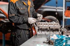 Il meccanico installa una nuova valvola Smonti il veicolo del blocco motore Riparazione del capitale del motore Sedici valvole e  fotografie stock libere da diritti