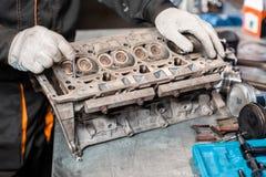 Il meccanico installa una nuova valvola Smonti il veicolo del blocco motore Riparazione del capitale del motore Sedici valvole e  fotografia stock libera da diritti