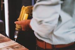 Il meccanico, l'uomo, sta utilizzando un trapano per perforare il legno nei lavori di costruzione fotografie stock