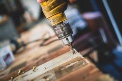 Il meccanico, l'uomo, sta utilizzando un trapano per perforare il legno fotografia stock