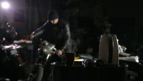 Il meccanico muove il vecchio motociclo nella sua officina per la riparazione archivi video