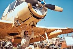 Il meccanico nel casco di volo e dell'uniforme ripara il retro museo militare dell'aeroplano all'aperto fotografie stock libere da diritti