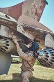 Il meccanico nel casco di volo e dell'uniforme ripara il vecchio combattente-intercettore di guerra in un museo all'aperto immagine stock libera da diritti
