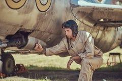 Il meccanico nel casco di volo e dell'uniforme ripara il vecchio combattente-intercettore di guerra in un museo all'aperto immagini stock