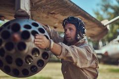 Il meccanico nel casco di volo e dell'uniforme ripara il vecchio combattente-intercettore di guerra in un museo all'aperto fotografia stock