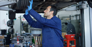 Il meccanico nel servizio dell'automobile, le riparazioni dello specialista l'automobile, fa la trasmissione e le ruote Concetto: fotografia stock