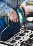 Il meccanico per mezzo di un trapano frantuma la valvola sul motore Fotografia Stock Libera da Diritti