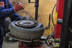 Il meccanico professionista che sostituisce la gomma sopra spinge dentro il servizio di riparazione dell'automobile fotografia stock