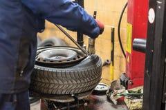 Il meccanico professionista che sostituisce la gomma sopra spinge dentro il servizio di riparazione dell'automobile fotografia stock libera da diritti