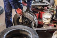 Il meccanico professionista che sostituisce la gomma sopra spinge dentro il servizio di riparazione dell'automobile fotografie stock