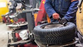Il meccanico professionista che sostituisce la gomma sopra spinge dentro il servizio di riparazione dell'automobile immagini stock