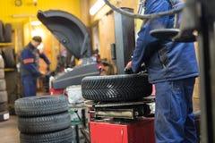 Il meccanico professionista che sostituisce la gomma sopra spinge dentro il servizio di riparazione dell'automobile immagini stock libere da diritti