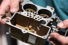 Il meccanico tiene il carburatore Fotografie Stock