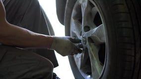 Il meccanico torce i bulloni sulle ruote dell'automobile stock footage