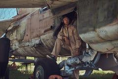 Il meccanico in uniforme e nel casco di volo effettua la manutenzione di vecchio bombardiere militare in un museo all'aperto fotografia stock