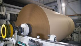 Il meccanismo annaspa carta d'imballaggio su rotolo enorme nella pianta video d archivio