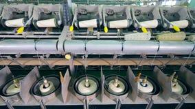 Il meccanismo moderno avvolge il filato sulle bugne bianche ad una fabbrica stock footage