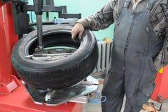 Il mechanician dell'automobile cambia un coperchio del pneumatico Immagini Stock Libere da Diritti