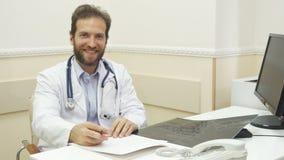 Il medico è scrivere raccomandazioni dopo il controllo dei raggi x fotografia stock