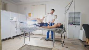 Il medico asiatico conduce la procedura di allungamento della spina dorsale, la chiroterapia, medicina tibetana asiatica Fotografie Stock
