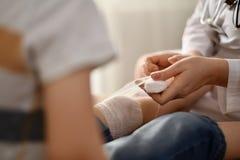 Il medico benda il ginocchio al paziente immagine stock