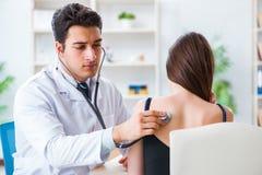 Il medico che controlla l'orecchio dei pazienti durante l'esame medico immagini stock libere da diritti