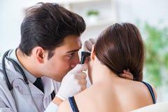 Il medico che controlla l'orecchio dei pazienti durante l'esame medico fotografia stock libera da diritti