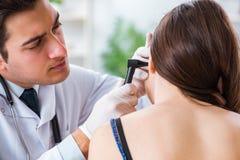 Il medico che controlla l'orecchio dei pazienti durante l'esame medico fotografie stock