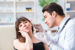 Il medico che controlla l'orecchio dei pazienti durante l'esame medico fotografia stock
