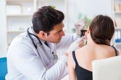 Il medico che controlla l'orecchio dei pazienti durante l'esame medico fotografie stock libere da diritti