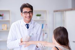 Il medico che esamina la pelle del paziente femminile Immagini Stock