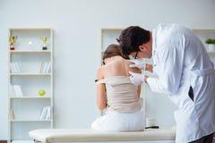 Il medico che esamina la pelle del paziente femminile Fotografie Stock Libere da Diritti