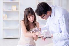 Il medico che esamina la pelle del paziente femminile Immagine Stock Libera da Diritti