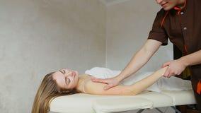 Il medico con esperienza del tipo applica manualmente il metodo manuale di massaggio per le mani del ` s della donna al paziente, video d archivio