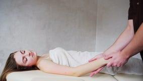Il medico con esperienza del tipo applica manualmente il metodo manuale di massaggio per le mani del ` s della donna al paziente, stock footage