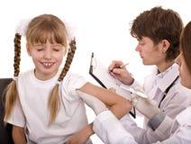 Il medico con la siringa inietta l'inoculazione al bambino. Immagini Stock Libere da Diritti