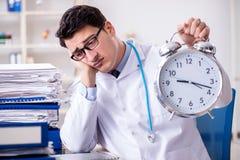 Il medico con la sveglia nel concetto urgente del controllo generale Immagine Stock