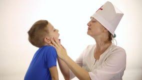 Il medico controlla la gola di un bambino malato stock footage