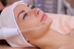 Il medico-cosmetologo fa la terapia di Microcurrent di procedura della pelle facciale di un bello, giovane donna Fotografia Stock