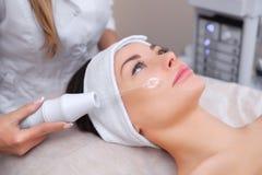 Il medico-cosmetologo fa la terapia di Microcurrent di procedura sui capelli di un bello, giovane donna fotografia stock libera da diritti